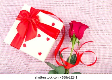 gift box and rose on a light background.