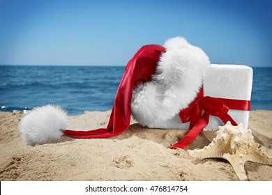 Gift box with Santa hat and sea star on beach. Christmas holiday concept