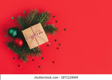Gift box with spruce branches and christmas balls on a red background with sparkles stars. Place for text. Flat lay.