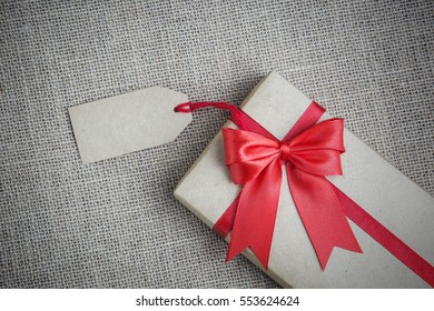 gift in box with tag and red bow on the burlap