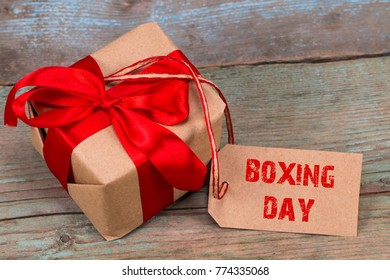 gift box and tag with a text: boxing day, on wooden background.