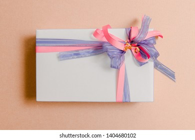 Gift box tied with blue and pink ribbons on pink background