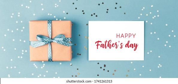 Boîte à cadeaux noué ruban bleu et carte de voeux du Joyeux Père sur fond bleu décoré de confettis. Vue en haut, concept vacances.