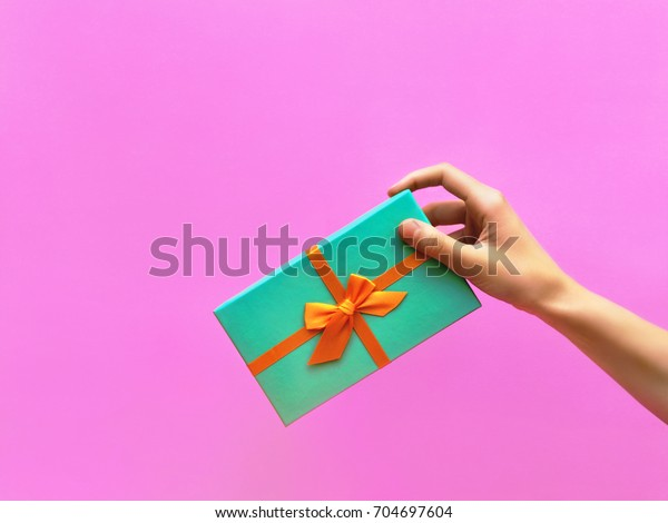 Gift box Trendy styled photo Female hand is holding a gift box against a lilac wall background Front view Modern pop art photo with space for text