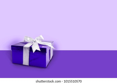 Gift box ultra violet color with white bow / ribbon  on a violet background with copy space.