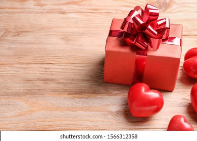 Gift box for Valentine's Day and red hearts on wooden background