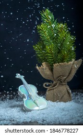 Gift box with violin on artificial snow. Christmas present. New Year concept, winter. Miniature copie of violin with Christmas tree