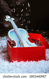 Gift box with violin on artificial snow. Christmas present. New Year concept, winter. Miniature copie of violin