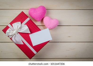 gift box with white bow and blank name card on wooden board background