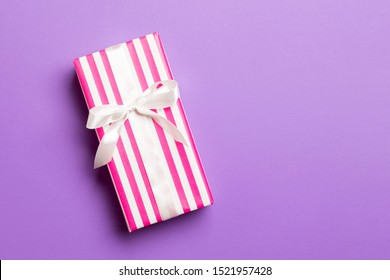 Gift box with white bow for Christmas or New Year day on purple background, top view with copy space.