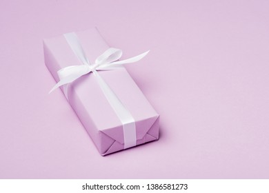 gift box with white ribbon on purple surface