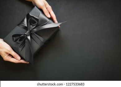 Gift box wrapped in black in female hand. Copy space. Top view. Black friday.