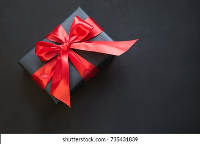 Gift box wrapped in black paper with red ribbon on black surface. Top view with copy space.