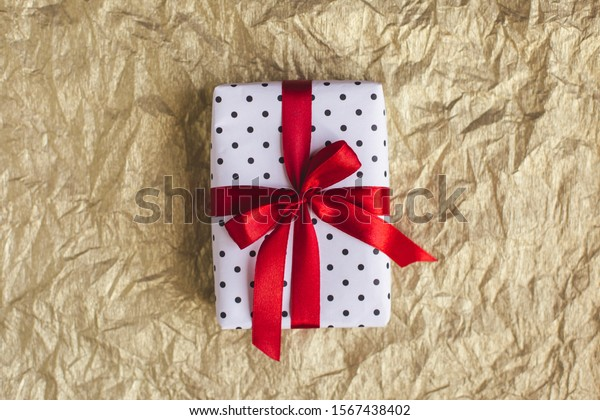 Gift box wrapped in black polka-dot white paper with red bow on golden foil  background. Holiday concept. Place for text.