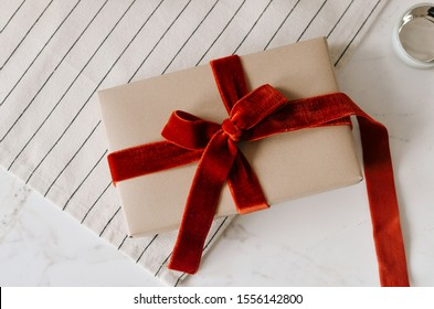 a gift in a box wrapped in brown craft paper with a red velvet ribbon on a bow on a white table with a striped serving napkin. Holiday gift