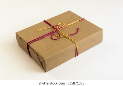 Gift box wrapped with brown paper with colored cotton string. Festive gift pack on white background.