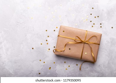 Gift box wrapped in craft paper with gold ribbon and stars on gray stone