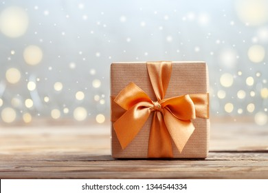 Gift box wrapped with craft paper and bow on neutral background with boke.