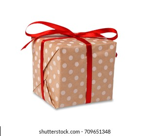 Gift box wrapped with dotted paper and red satin ribbon, isolated on white background. Modern present for any holiday, christmas, valentine or birthday
