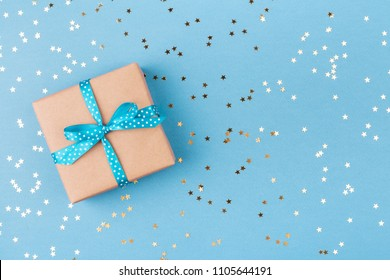 Gift box wrapped in kraft paper and tied with turquoise ribbon on blue background decorated with confetti. Top view, holiday concept.