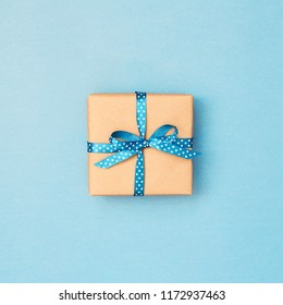 Gift box wrapped in kraft paper tied with blue ribbon in polka dots on blue background. Minimal stiled reeting card.