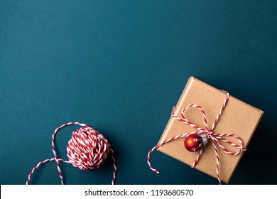Gift box wrapped in kraft paper and tied with candy cane Christmas rope on dark blue background. Holiday concept, top view.