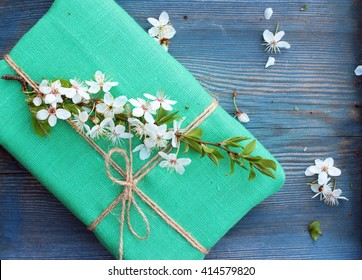 Gift box wrapped with natural linen cloth and decorated with spring flowers. Floral decor elements/ Rustic design