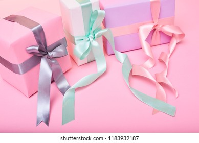 Gift box wrapped  paper with pink ribbon and wrapping materials on a pink old background. Vintage style.