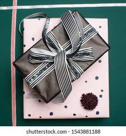 Gift box wrapped in paper with ribbon, wrapping materials, and scabiosa on a green background