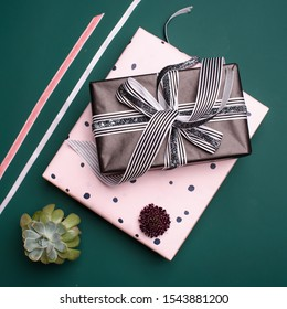 Gift box wrapped in paper with ribbon, wrapping materials, succulent and scabiosa on a green background