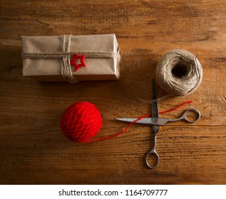 gift box wrapped in recycled craft paper, with ribbon and star.  scissors and red skein.