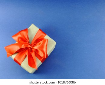 gift box wrapped in recycled paper with ribbon bow isolated on blue background