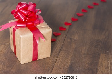 Gift box wrapped in recycled paper with red ribbon bow on a background of red hearts.