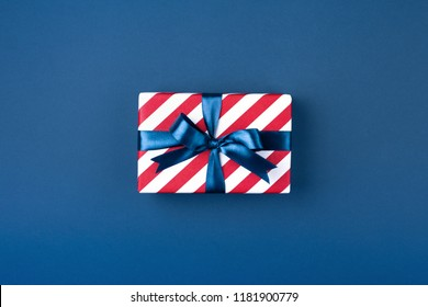 Gift box wrapped in red striped paper and tied with blue bow on dark blue background. Holiday concept, top view.