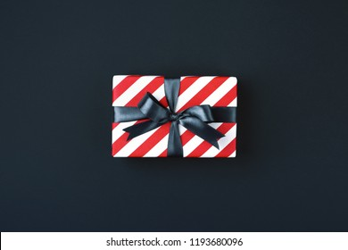 Gift box wrapped in red striped paper and tied with black bow on black background. Black friday and cyber monday concept, top view.