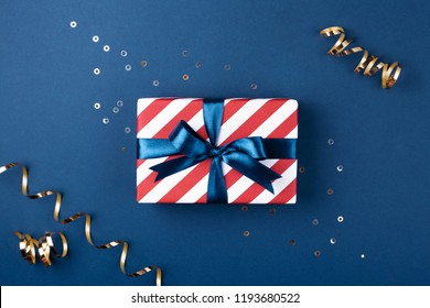 Gift box wrapped in red striped paper and tied with blue bow on blue background decorated with sparkles and golden serpentine. Christmas card concept.