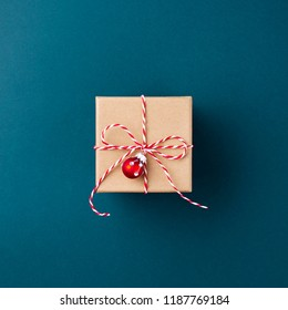 Gift boxe wrapped in kraft paper tied with candy cane Christmas rope on dark blue background. New Year concept, top view, minimal styled.