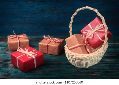 Gift boxes in basket over blue wooden background.
