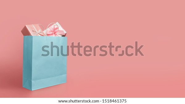 Gift boxes in blue paper shopping bag on isolated pink background with copy space. Black Friday, Sales, Giving Gift for Christmas and New Year 2019.