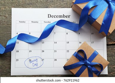 Gift boxes and calendar list on wooden table. Boxing day concept