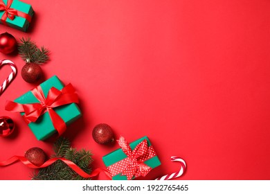 Gift boxes and Christmas decorations on red background, flat lay. Space for text