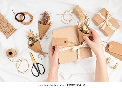 Gift boxes in craft paper and natural decorations, creative and zero waste holidays present wrapping. Womens day, mothers day, easter greeting concept. Top view, flat lay