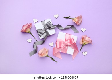 Gift boxes with eustoma flowers on purple background