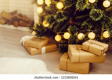Gift boxes with a large red bow against a background bokeh of twinkling party lights. Luxury New Year gift. Christmas gift. Christmas background with gift box. Christmastime celebration