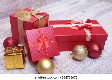 Gift boxes with many christmas balls on wood background.