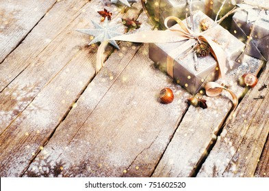 Gift boxes on old wooden background with silver stars, cones, hazelnut, anise, tape, ribbon, snowflakes. Top view, copy space, light bokeh, snow effect, toned