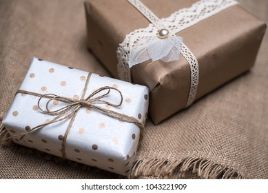 Gift boxes on the table decorated with lace. Beautiful gifts of Kraft paper and rope. A gift for a girl on holiday.