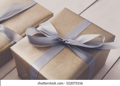 Gift boxes on white wood background. Presents in gold paper decorated with stylish elegant silver satin ribbon bows. Christmas and any other holidays concept