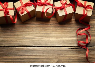 Gift Boxes on Wood Background, Holiday Cardboard Presents on Brown Wooden Birthday Decoration, Red Ribbon