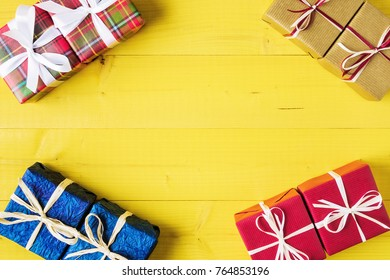 Gift boxes over yellow wooden background with copy space.